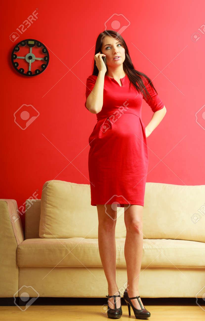 3cdff5d51 Chica guapa con estilo en el vestido rojo. Mujer embarazada que habla en el  teléfono
