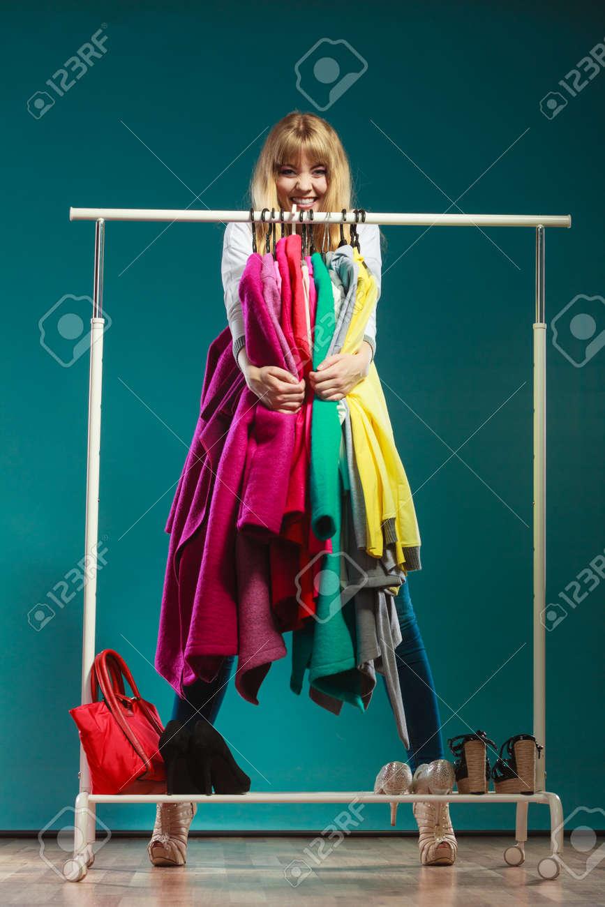 estilo clásico de 2019 ventas especiales otra oportunidad Mujer divertida niña feliz teniendo el acaparamiento de todos ropa abrigos  y camisas en el armario. Chica joven de compras en el centro comercial. ...
