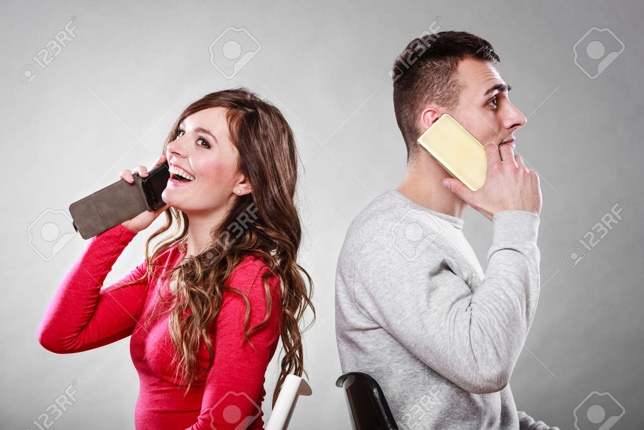 Young couple talking on mobile phones sitting back to back  Happy
