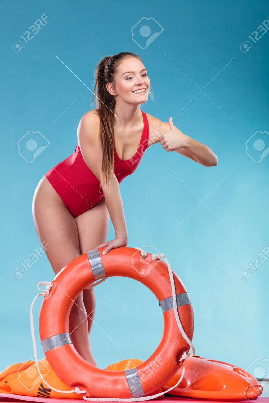 492a3e9df5e7 Happy lifeguard with ring buoy lifebuoy. Woman girl supervising swimming  pool water giving thumb up