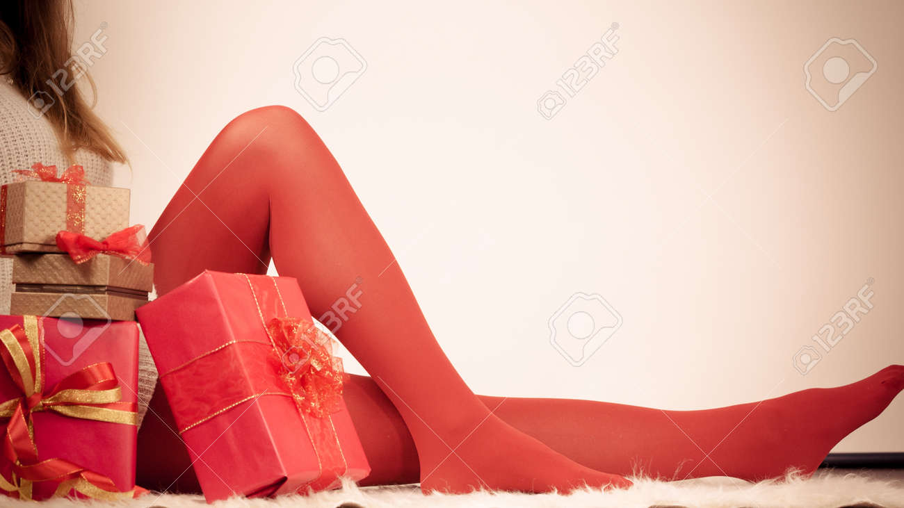 Christmas winter happiness concept. Woman legs wearing red pantyhose..