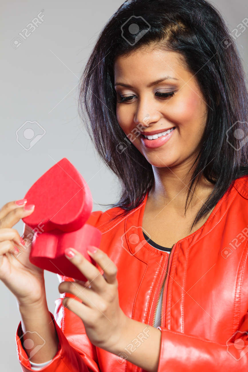 Valentines Day concept. Lovely cute african girl in stylish red jacket holding heart box gift present. Love time. - 121451569