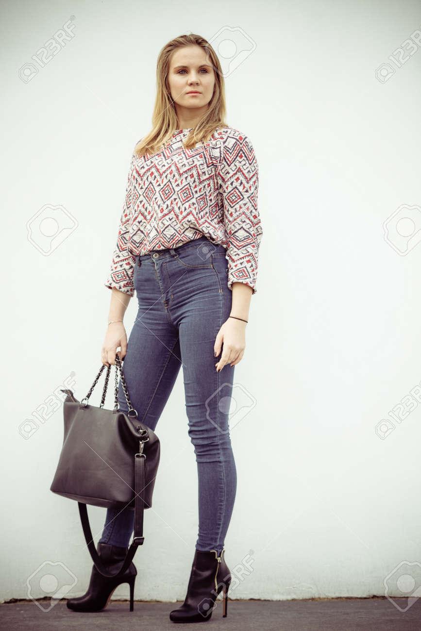 Estilo urbano. mujer de belleza con estilo de moda con el bolso del bolso negro. Blondie niña modelo que presenta afuera. La manera de la hembra idea.