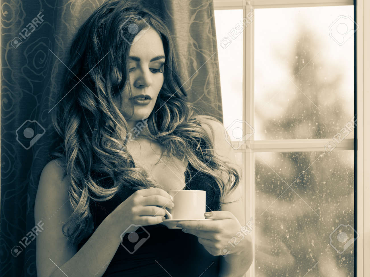 d6fdcbe2f352 Sensual seductive woman in lingerie drinking cup of coffee by curtain and  french door window at