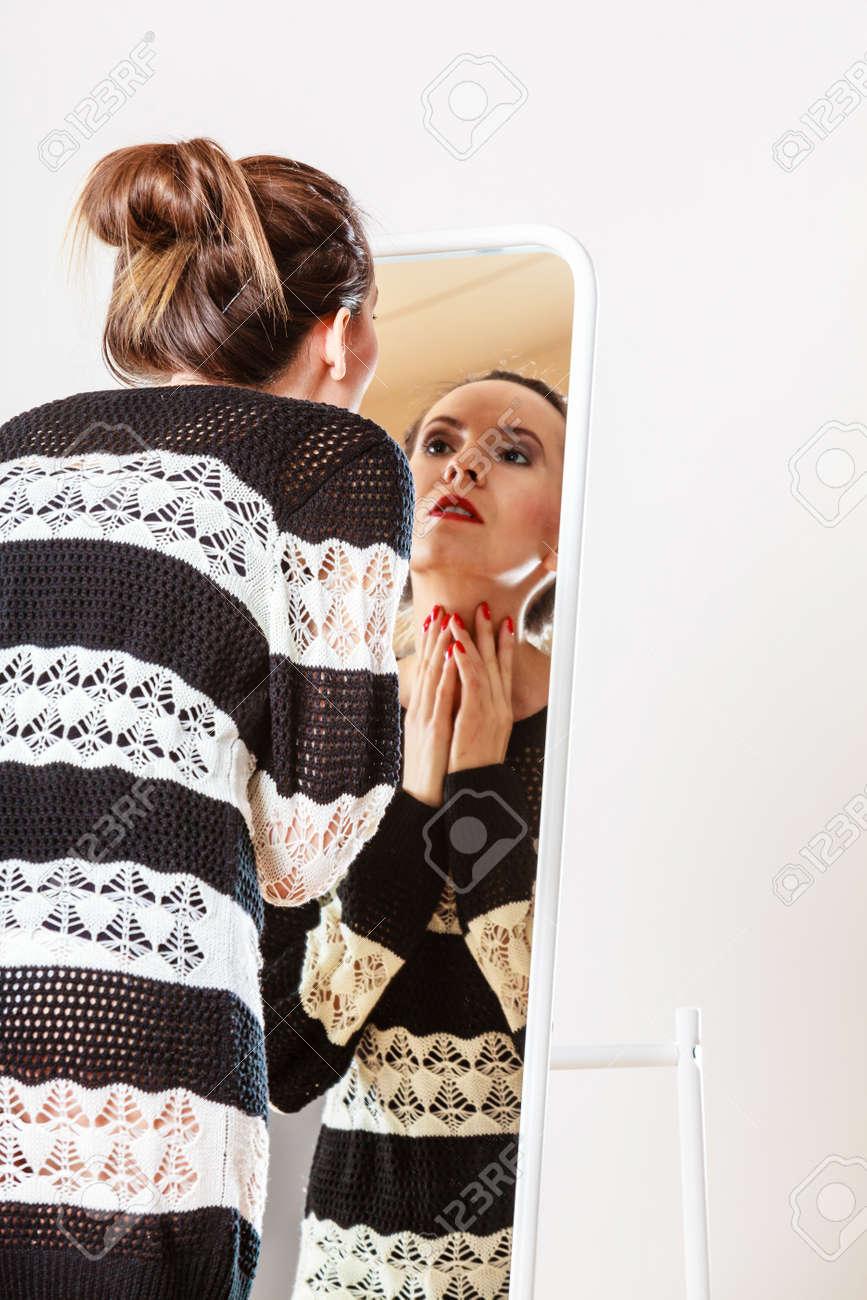 Archivio Fotografico - Moda e shopping. Donna che prova maglione vestito  scegliere vestiti. Attraente Cliente femminile guardando nello specchio 828094a8382