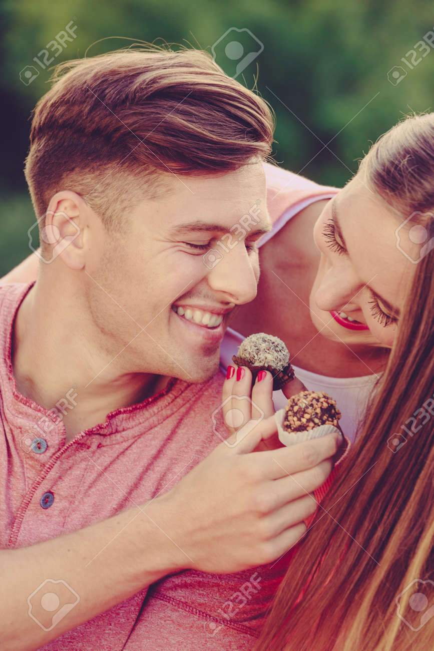 Love and happiness. Cute lovely lovers feeding each other by cupcakes cookies. Smiling couple with sweet food having fun. - 121457645