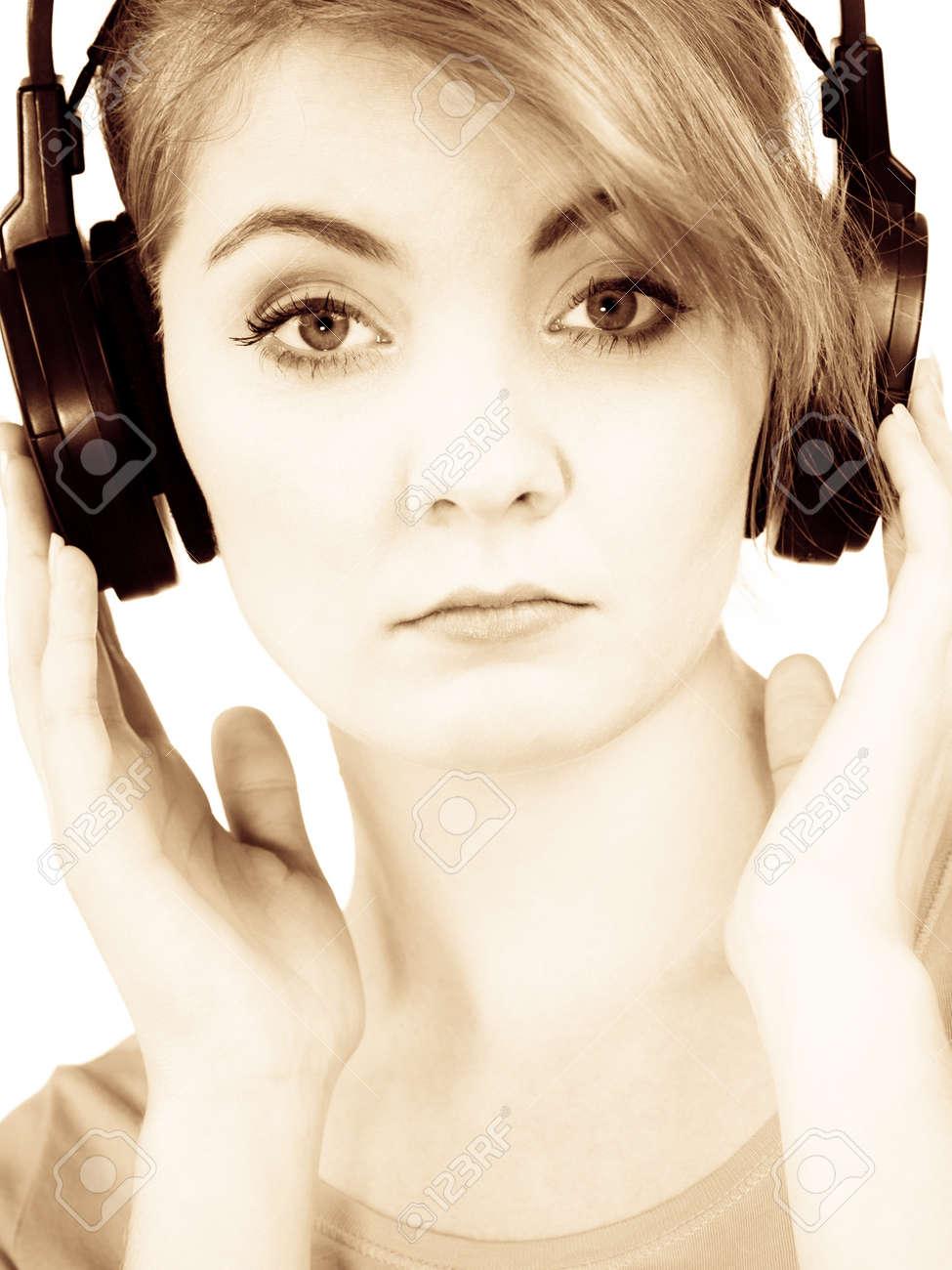 Woman sad unhappy girl in big headphones listening music mp3