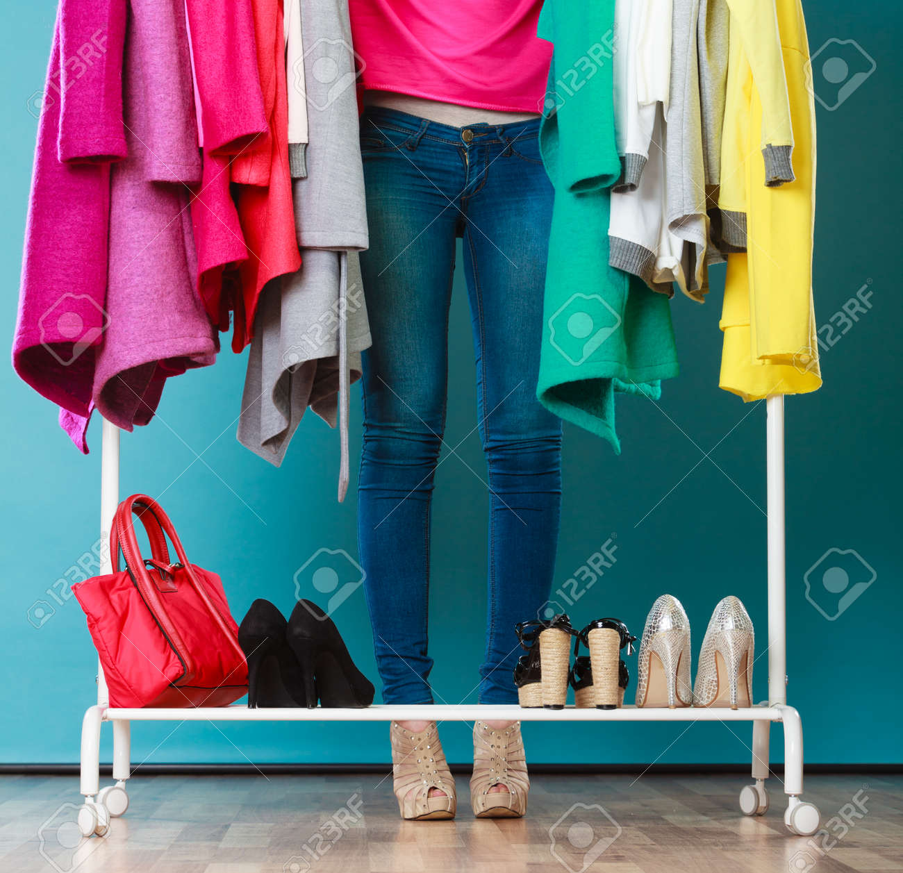 Closeup of woman choosing clothes to wear in wardrobe. Girl customer shopping in mall shop. Fashion clothing sale concept. - 54558848