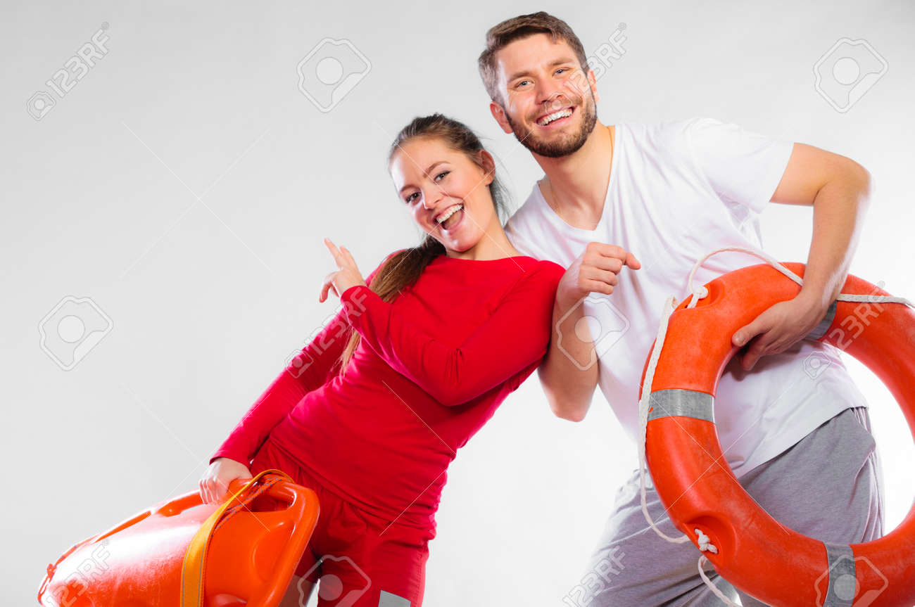3d54bd987a0 ... float lifesaver equipment having fun on gray. Accident prevention and water  rescue. Young man and woman lifeguard couple on duty holding ring