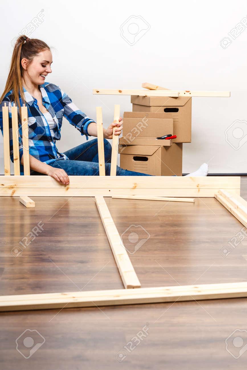 Femme se déplaçant dans montage de meubles au nouveau domicile. Jeune fille  organisation intérieure appartement de maison et boîtes déballage.