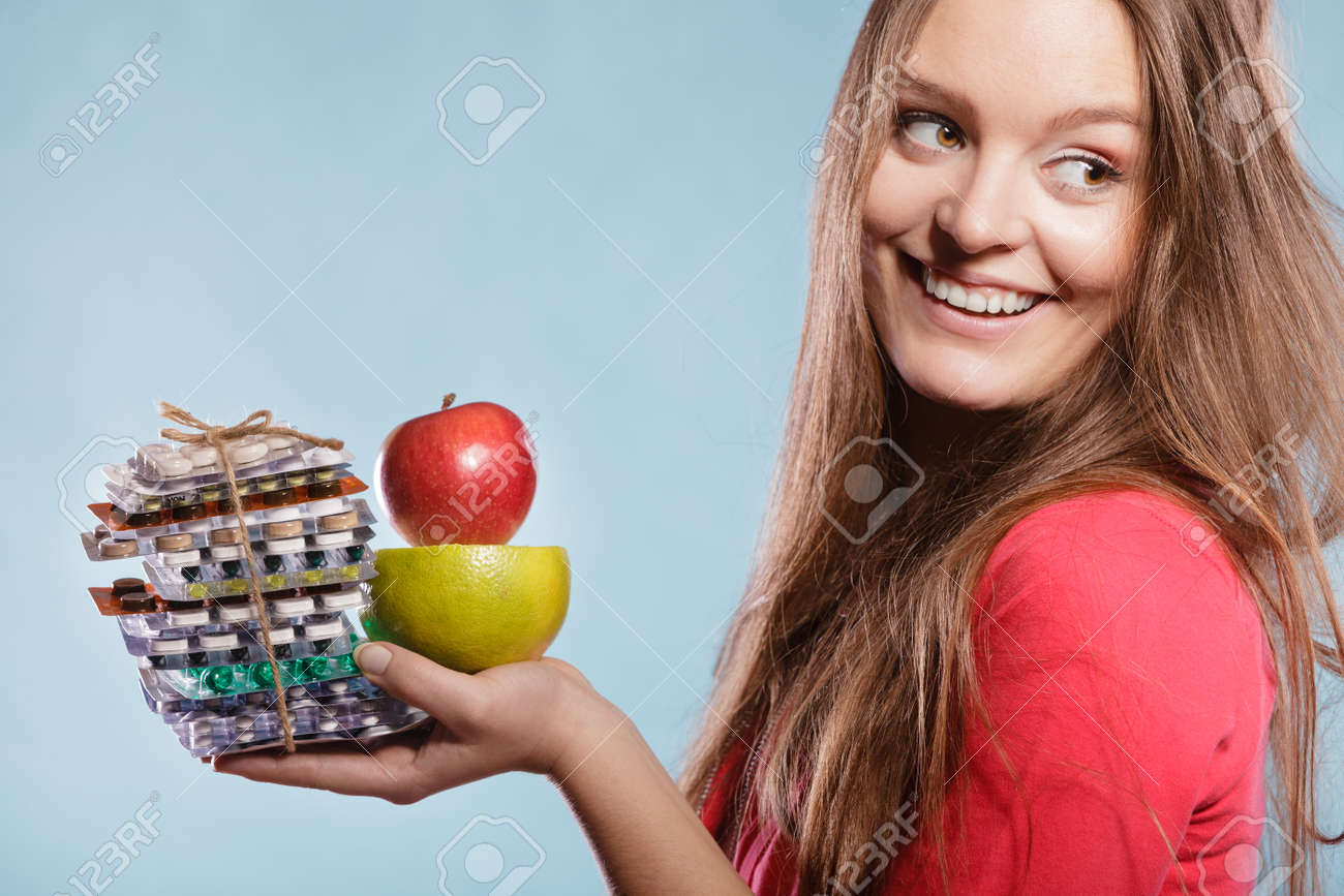woman girl holding vitamin tablets pills and fruits choice between