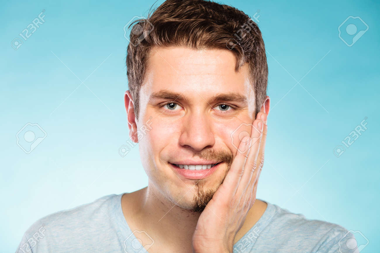 Portrait of happy man with half shaved face beard hair. Smiling handsome  guy on blue