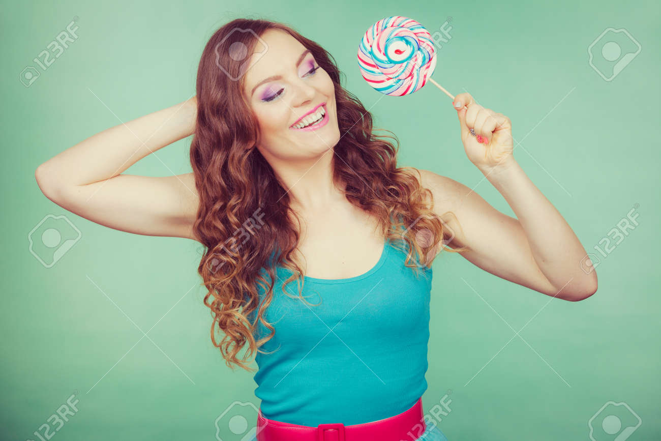 53628d93c98 Stock Photo - Woman attractive cheerful girl holding colorful lollipop  candy in hand. Sweet food and enjoying concept. Studio shot green blue  background, ...