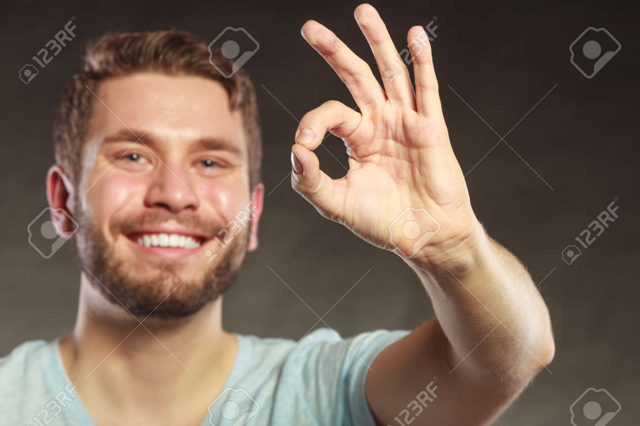 portrait of happy smiling handsome man guy giving ok okay sign