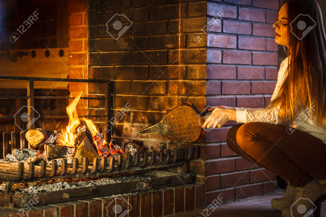 Woman At Fireplace Making Fire With Bellows Young Girl Heating