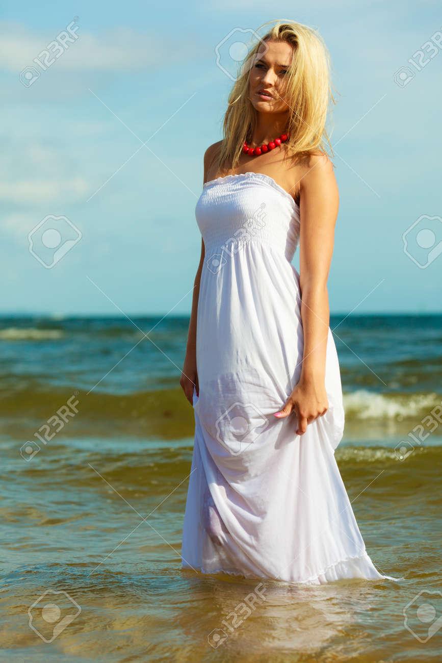 671841e75cb9 Giovane donna rilassarsi sulla spiaggia. Lady trascorrere momenti liberi al  di fuori. La ragazza attraente ha vestito bianco.