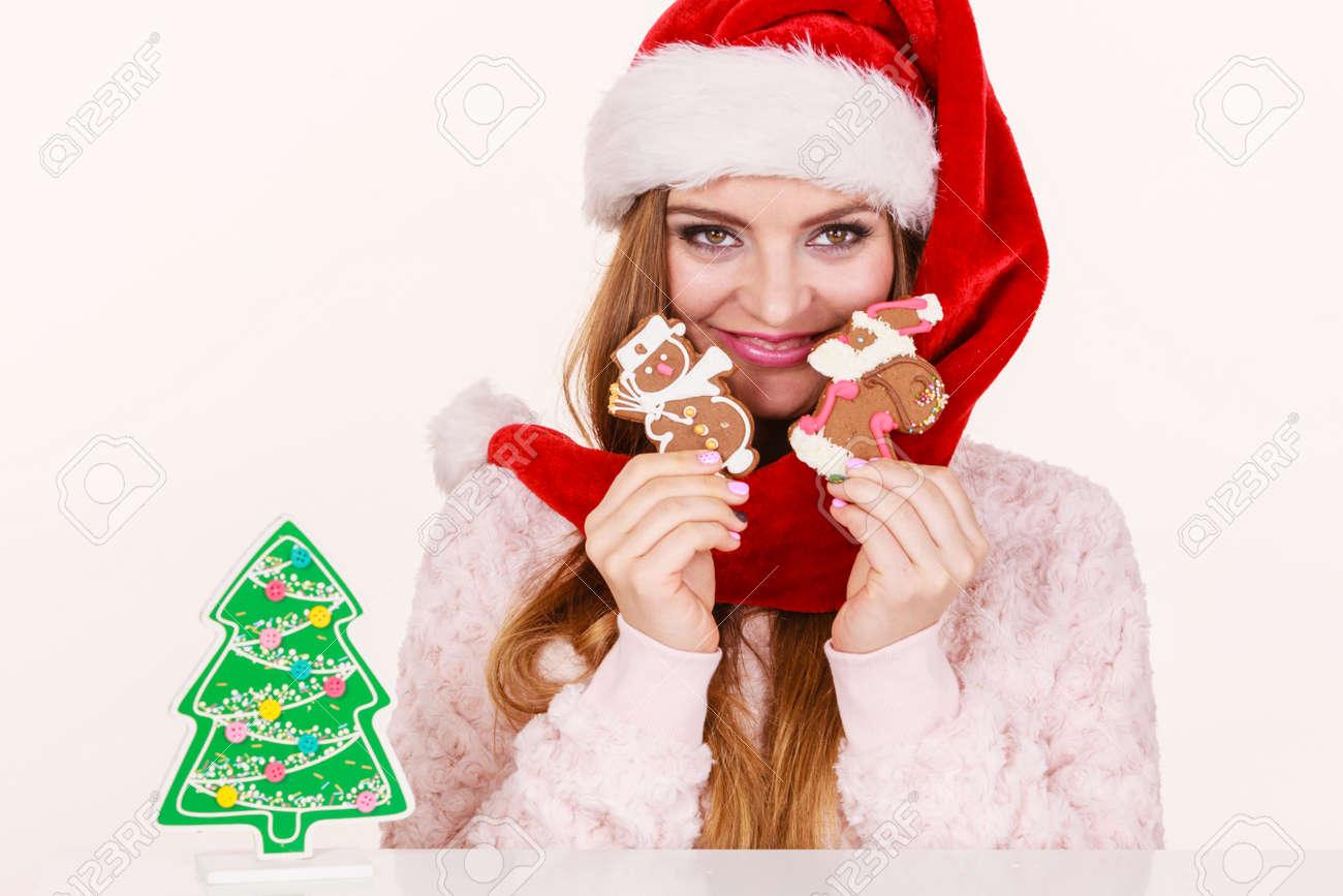 Foto de archivo - Mujer con sombrero rojo de Navidad jugando con galletas  de jengibre pequeño muñeco de nieve y Papá. niña feliz a la espera de las  ... 9f3129f4b41