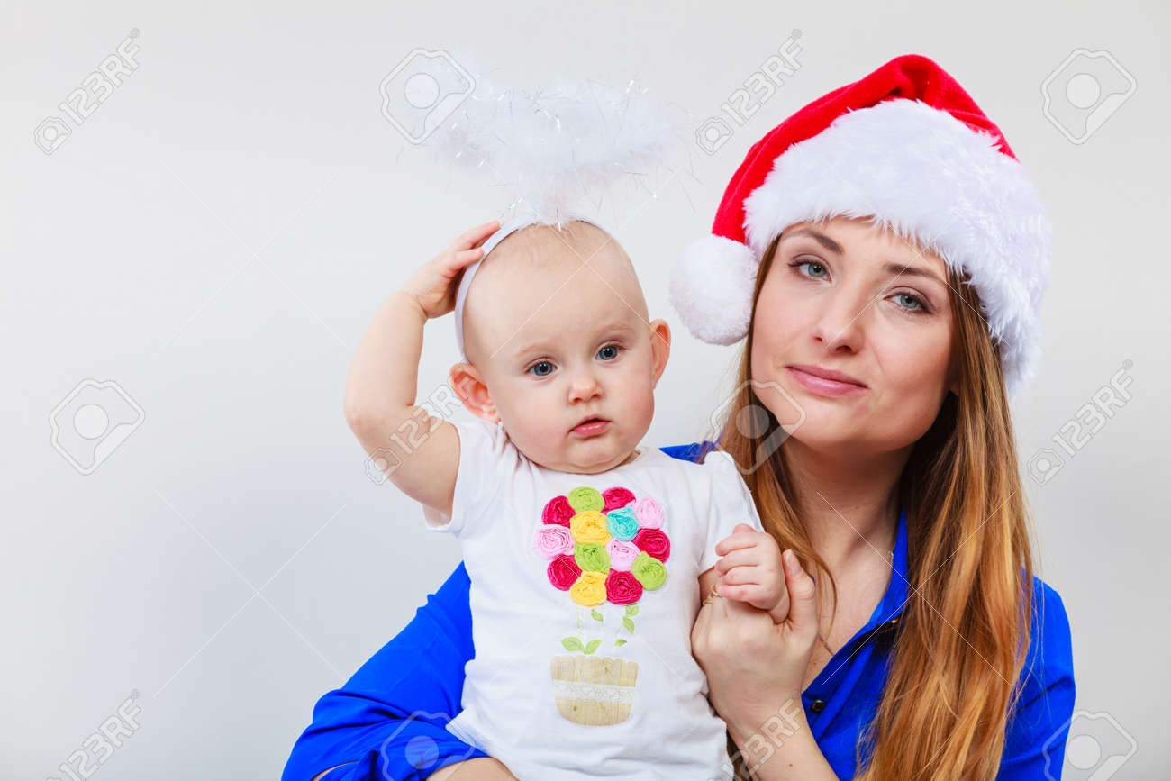 35973b3c62b06 Christmas woman with cute baby. Beautiful lady has red santa claus