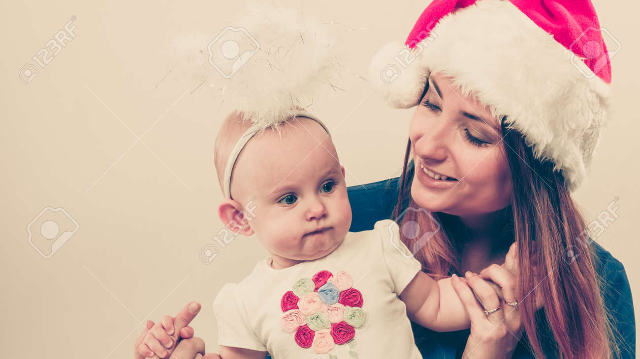 e54040ff65a Christmas woman with cute baby. Beautiful lady has red santa claus