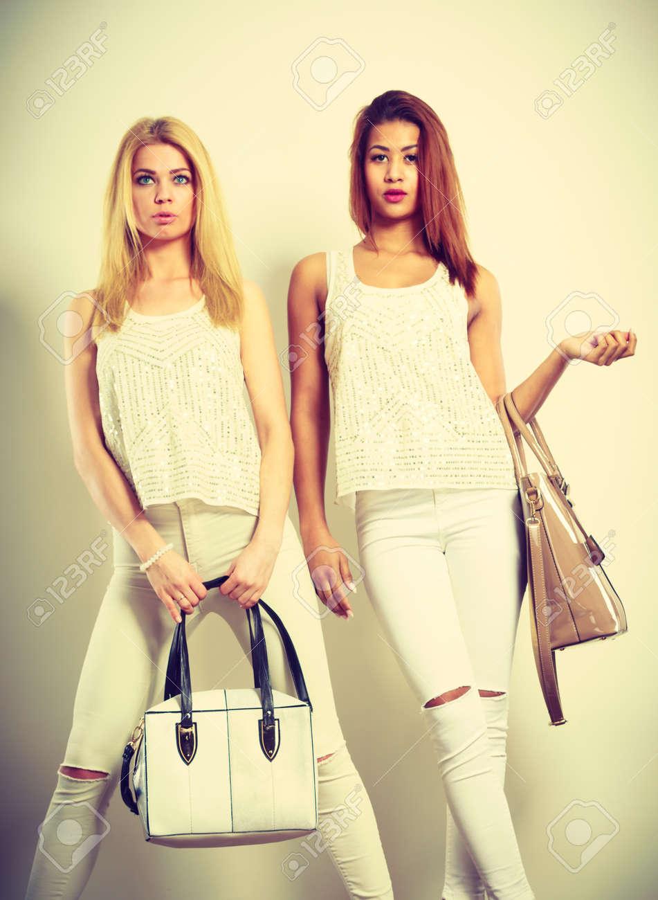 cbec088e1255 Prendas de vestir accesorios de moda para damas. Una foto de dos jóvenes  modelos con bolsos de mano. niñas atractivas vistiendo la misma ropa blanca.