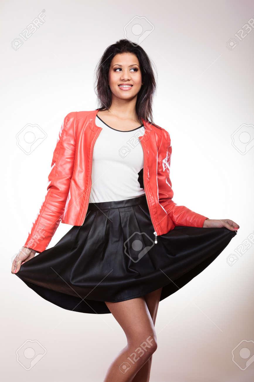 the latest d5130 78ff1 Moda e stile. Bellezza splendida giovane donna di razza mista indossando  cappotto giacca rossa elegante e gonna di pelle nera. Ragazza alla moda che  ...