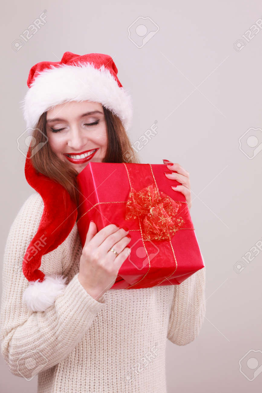8dac8b8541f Gorgeous woman wearing santa claus hat holding red big gift box with  ribbon. Xmas