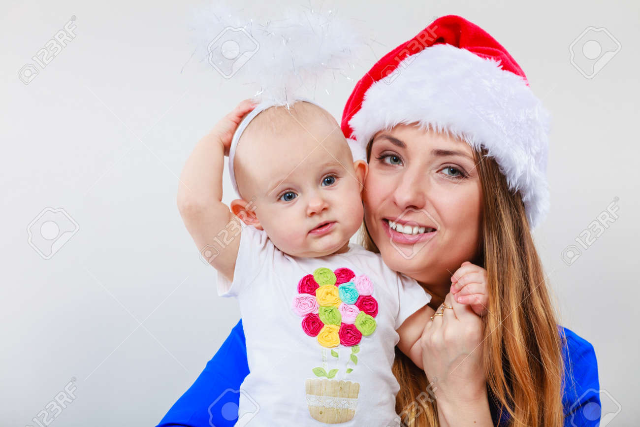 66fa5317b Christmas woman with cute baby. Beautiful lady has red santa claus