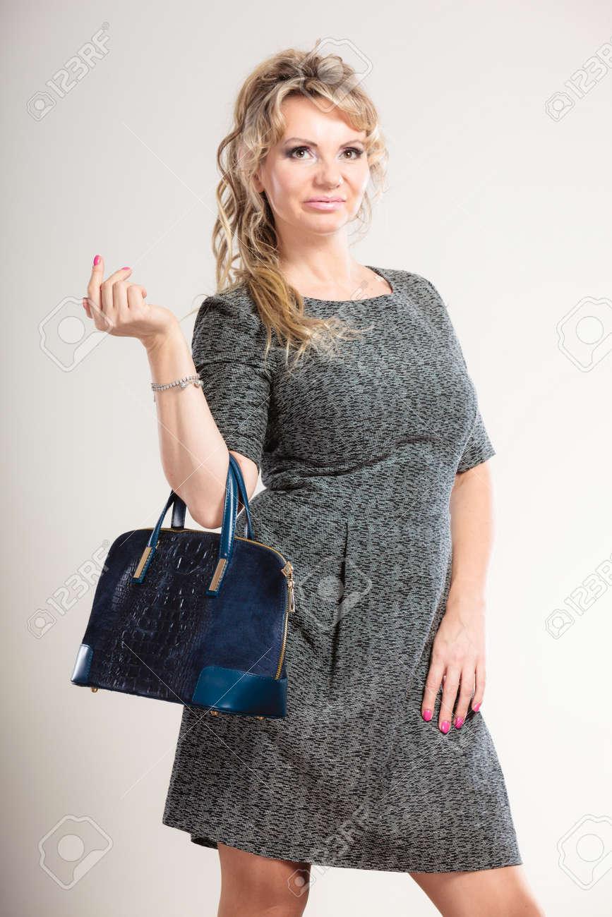 check out cb722 242ee Les femmes notion accessoires de mode. dame d'âge mûr avec sac à main.  Attractive femme avec une robe grise et a de longs cheveux blonds.