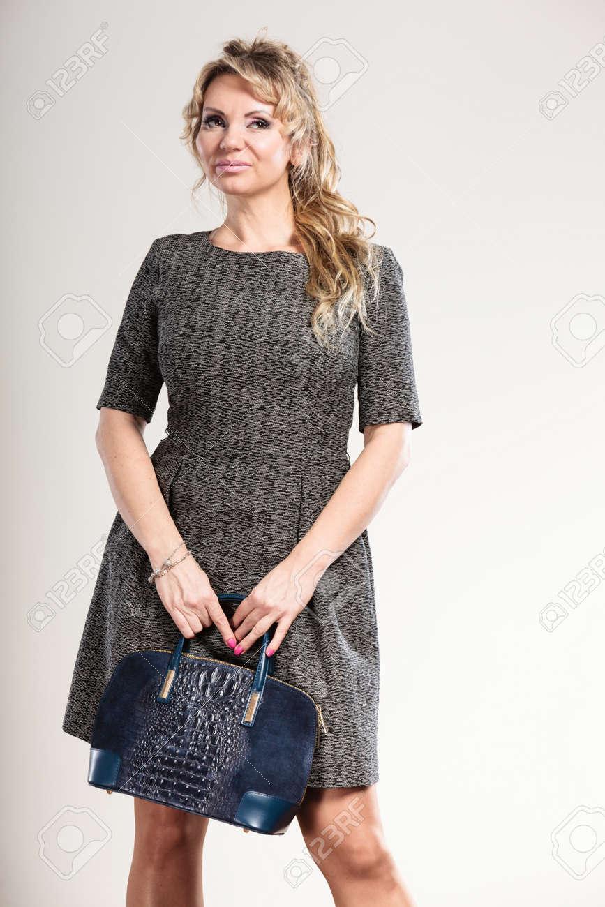 Las mujeres concepto de accesorios de moda. Señora madura con el bolso. Mujer atractiva con un vestido gris y tiene el pelo rubio y largo.