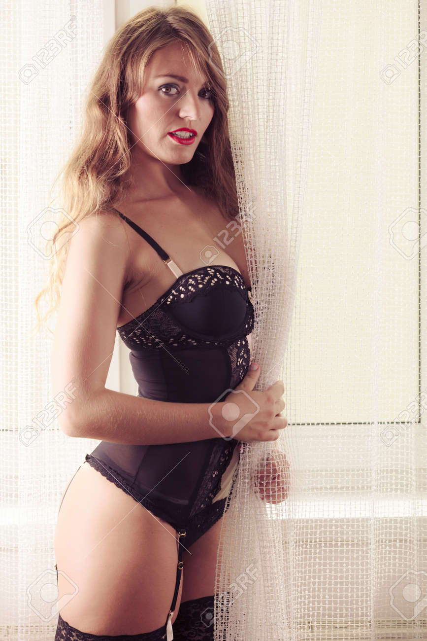 71a1e00d621 Sensual seductive attractive woman in lingerie posing by window with  curtain at home. Stock Photo