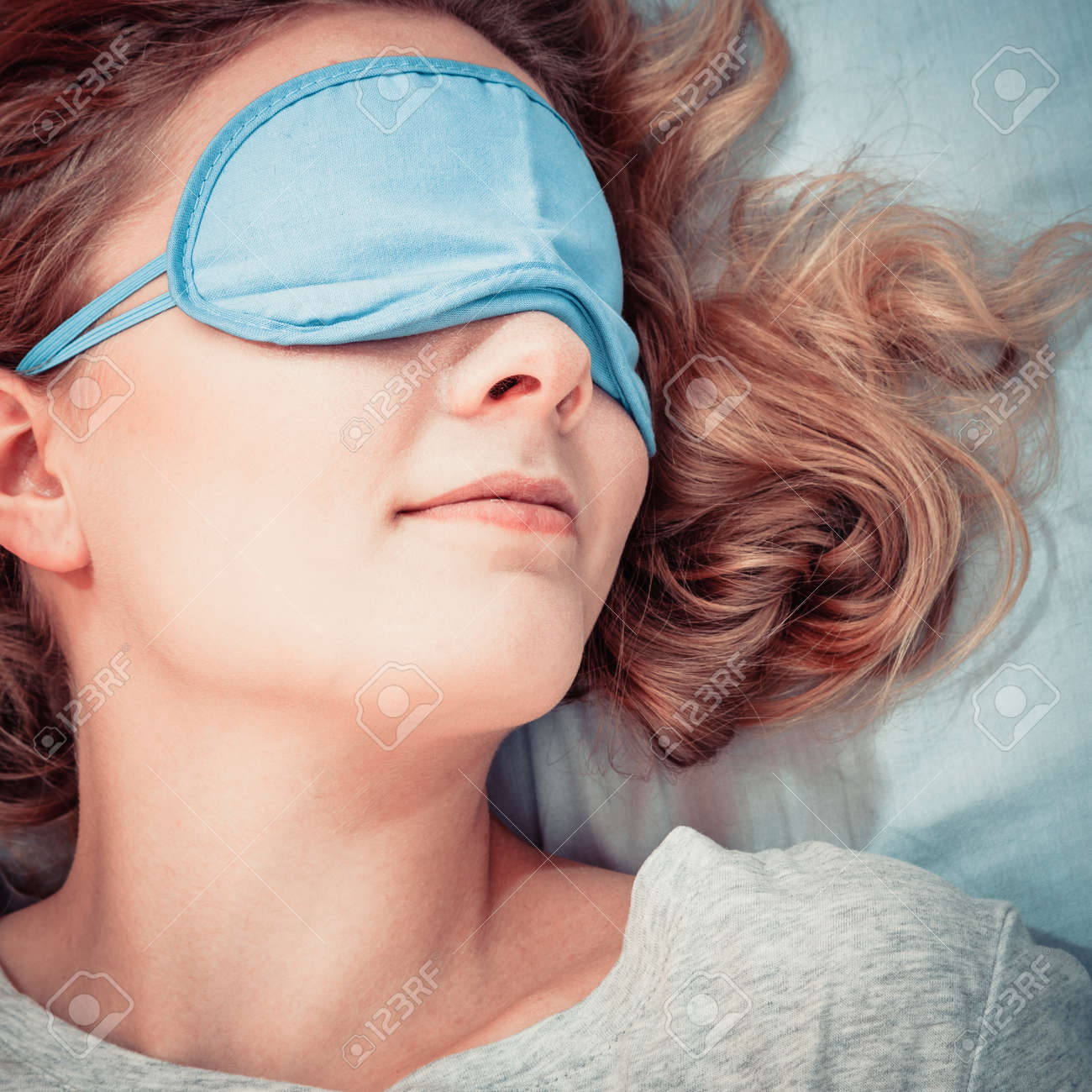 ef92561dda8 Stock Photo - Tired woman sleeping in bed wearing blindfold sleep mask. Young  girl taking nap.