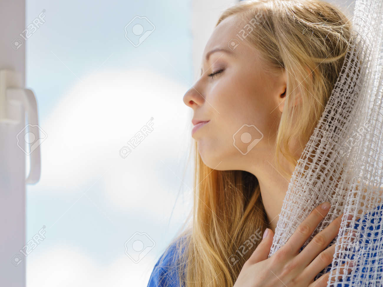 Happy woman with long blonde hair sitting on windowsill and relaxing, meditate or thinking holding white lace curtain. - 90618911