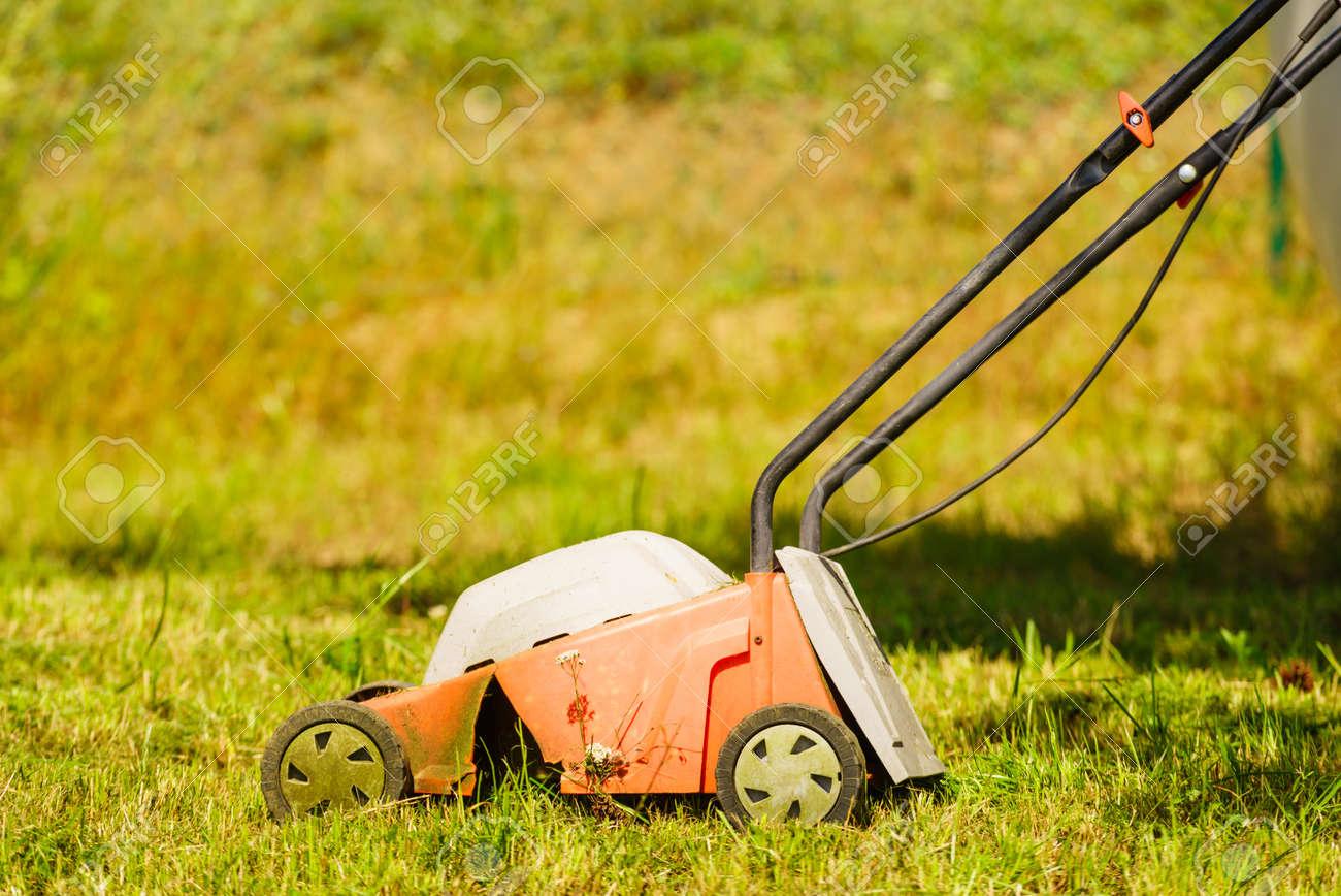 Gardening, Garden Service. Old Lawn Mower Cutting Green Grass In Backyard.  Mowing Field
