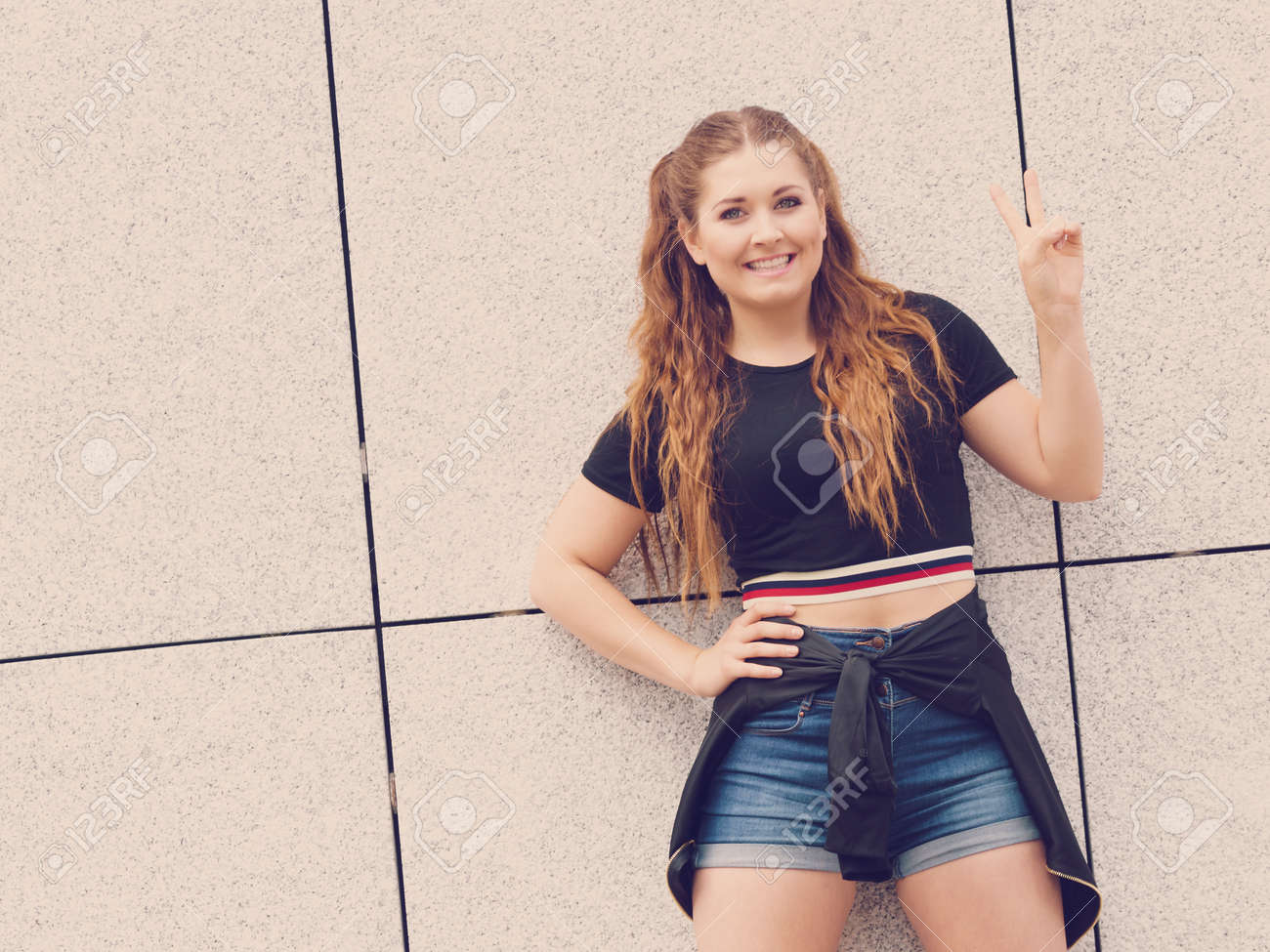 331555f192ba Stock Photo - Young teenage woman wearing denim shorts and black crop top. Female  presenting fashionable summer outfit.