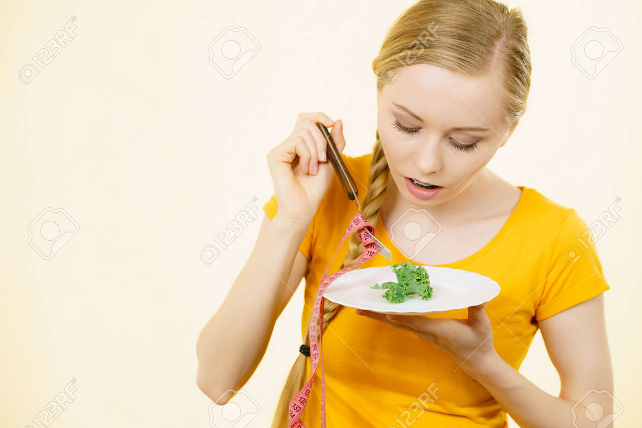 Sad Young Blonde Woman Dealing With Anorexia Nervosa Or Builimia Having Small Green Vegetable On Plate
