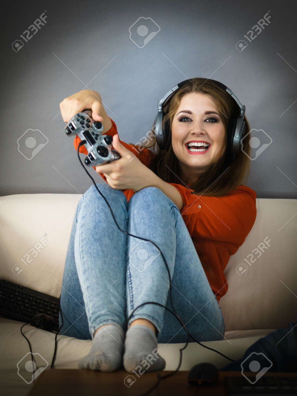 Nerd Geek Young Adult Women Playing On The Video Console Holding Game Pad Sitting On Sofa
