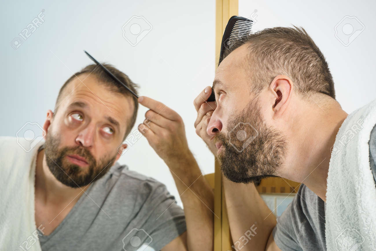 Adult man standing in front of the bathroom mirror brushing his..