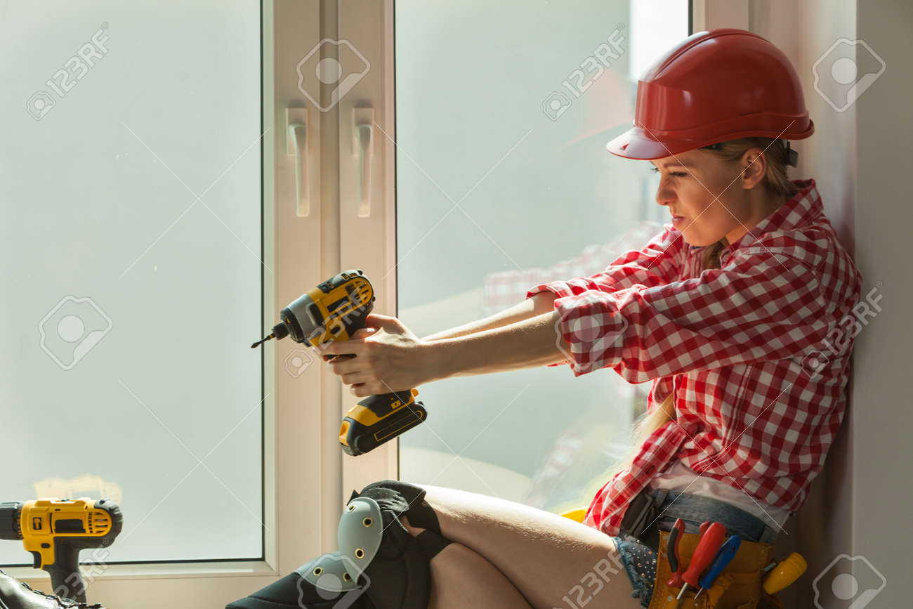 Young Woman Wearing Helmet Using Power Drill And Tools For Work At
