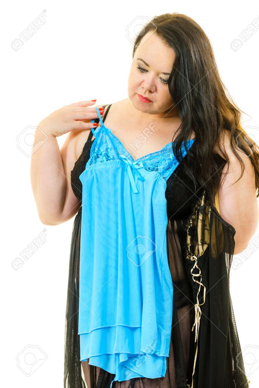 491b277ff8ee Mature adult woman wearing satin lingerie picking nightwear sleepwear. Plus  size female feeling comfortable wearing