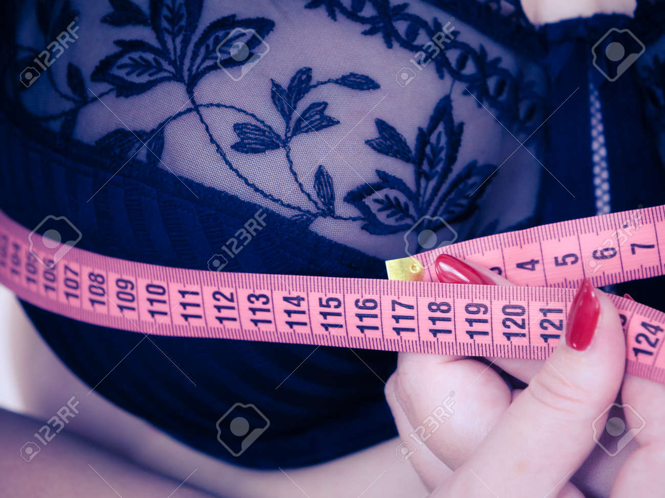 Plus size fat woman wearing black bra using tape measure to check the measurements of her big chest breasts. Closeup part of female body. Bosom, brafitting and underwear concept. - 117281685