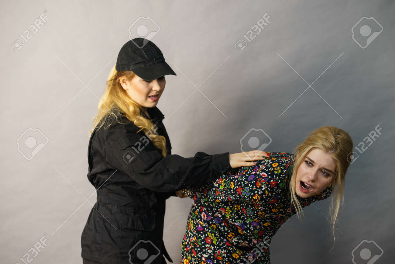Shoplifting is a crime. Young fashionable woman being caught on stealing clothes by female security guard. Customer being thief. - 140963550