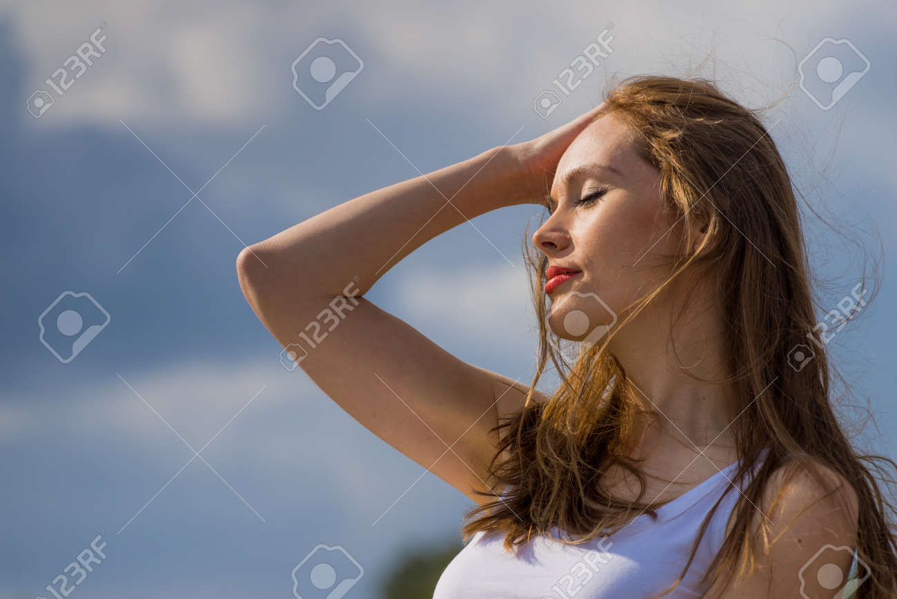 Young woman relaxing outdoor. Female enjoy sunlight against blue sky. - 143016100