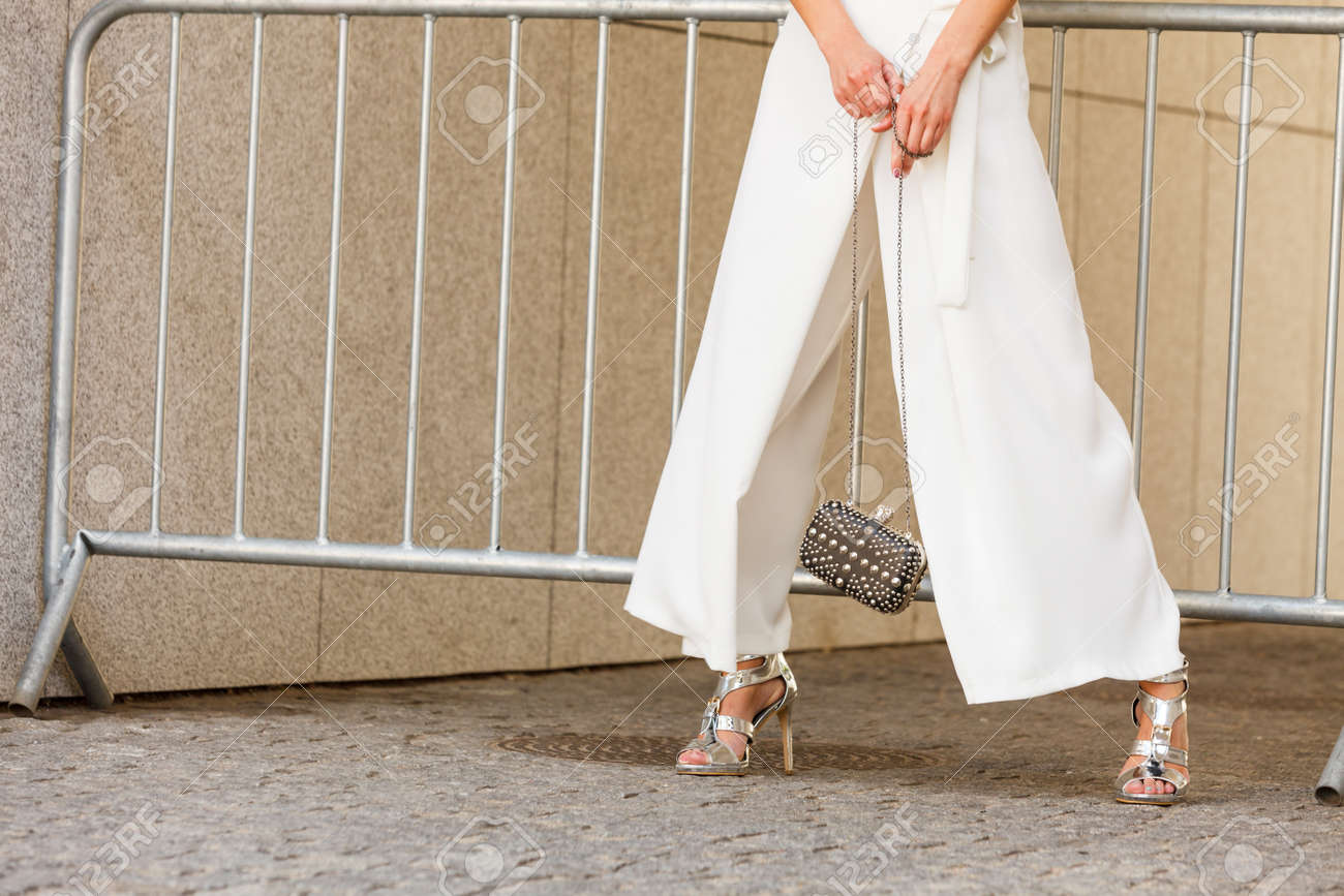 Unrecognizable woman wearing fashionable outfit. Close up at silver high heels, white culottes trousers and small black bag purse with pearls - 148381022