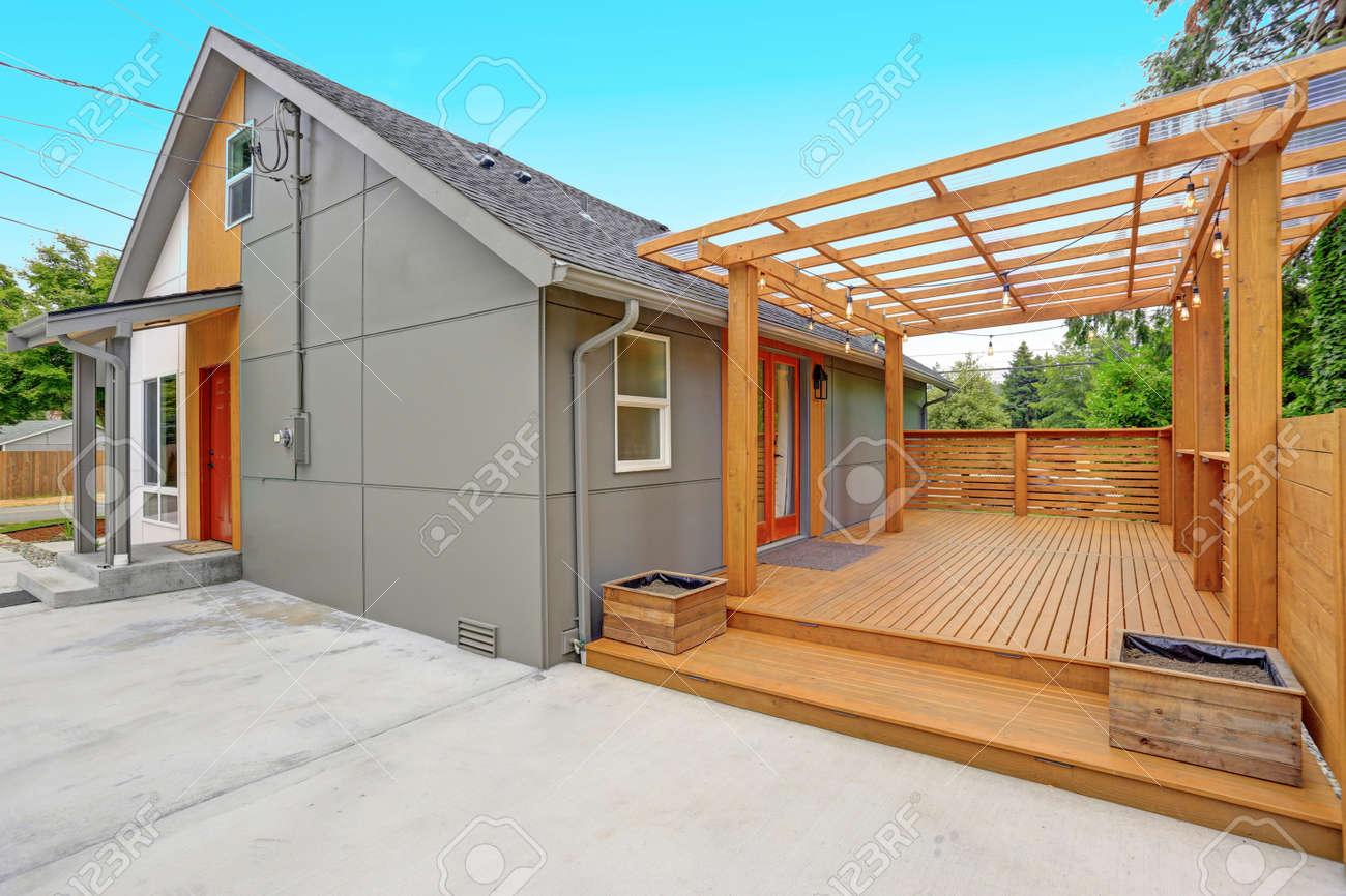Maison moderne entièrement rénovée à Everett, WA. Vue sur la cour arrière  avec un patio en béton spacieux et une grande terrasse envelopper.