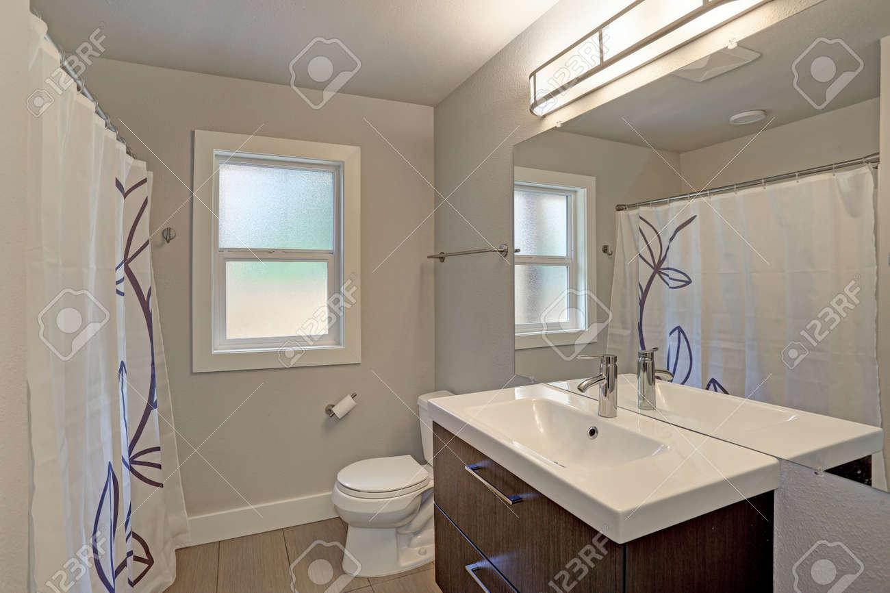 Salle De Bain En Longueur intérieur de la salle de bain fraîchement rénové avec un seul meuble-lavabo  surmonté de quartz blanc sous un miroir sans cadre pleine longueur monté