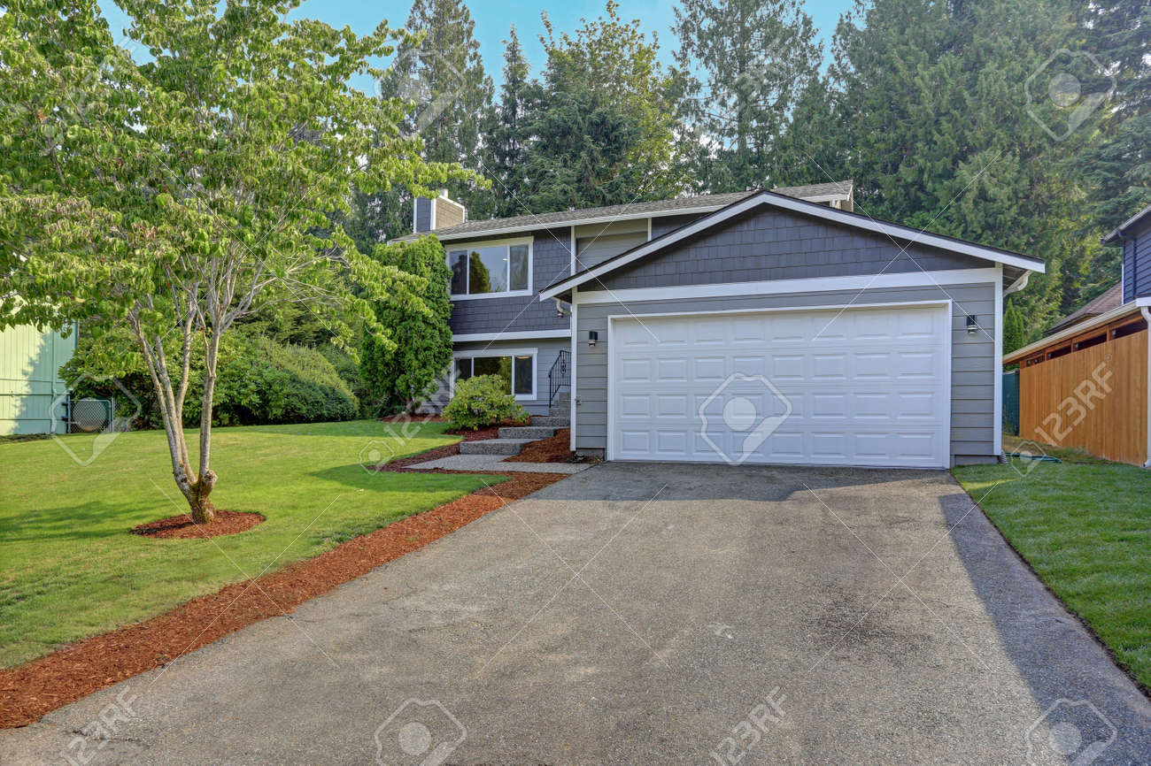 Lovely grey rambler house exterior features grey siding accented with white moldings, attached garage with asphalt driveway and well manicured front yard. Kirkland, WA, USA. - 111724610