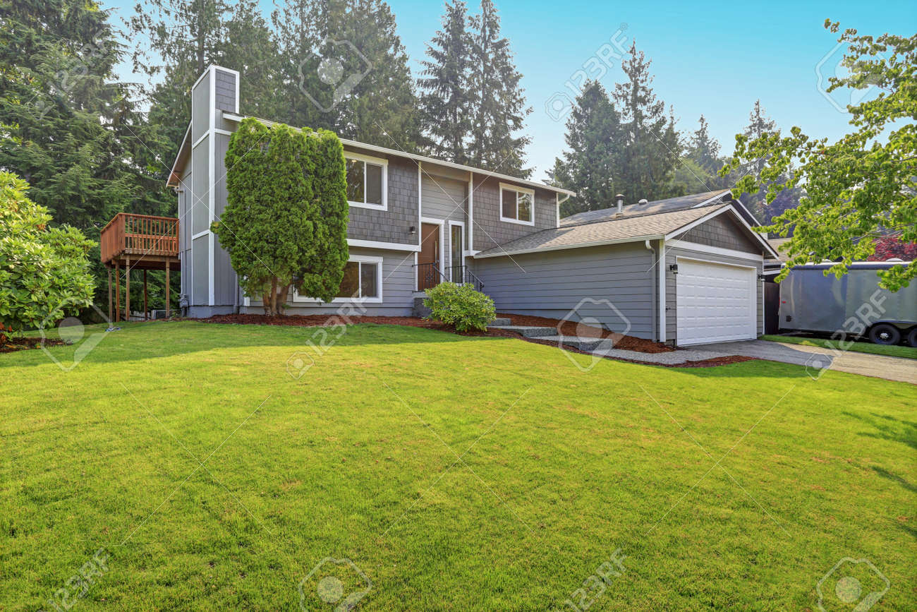 Lovely grey rambler house exterior features grey siding accented with white moldings, attached garage with asphalt driveway and well manicured front yard. Kirkland, WA, USA. - 111724612