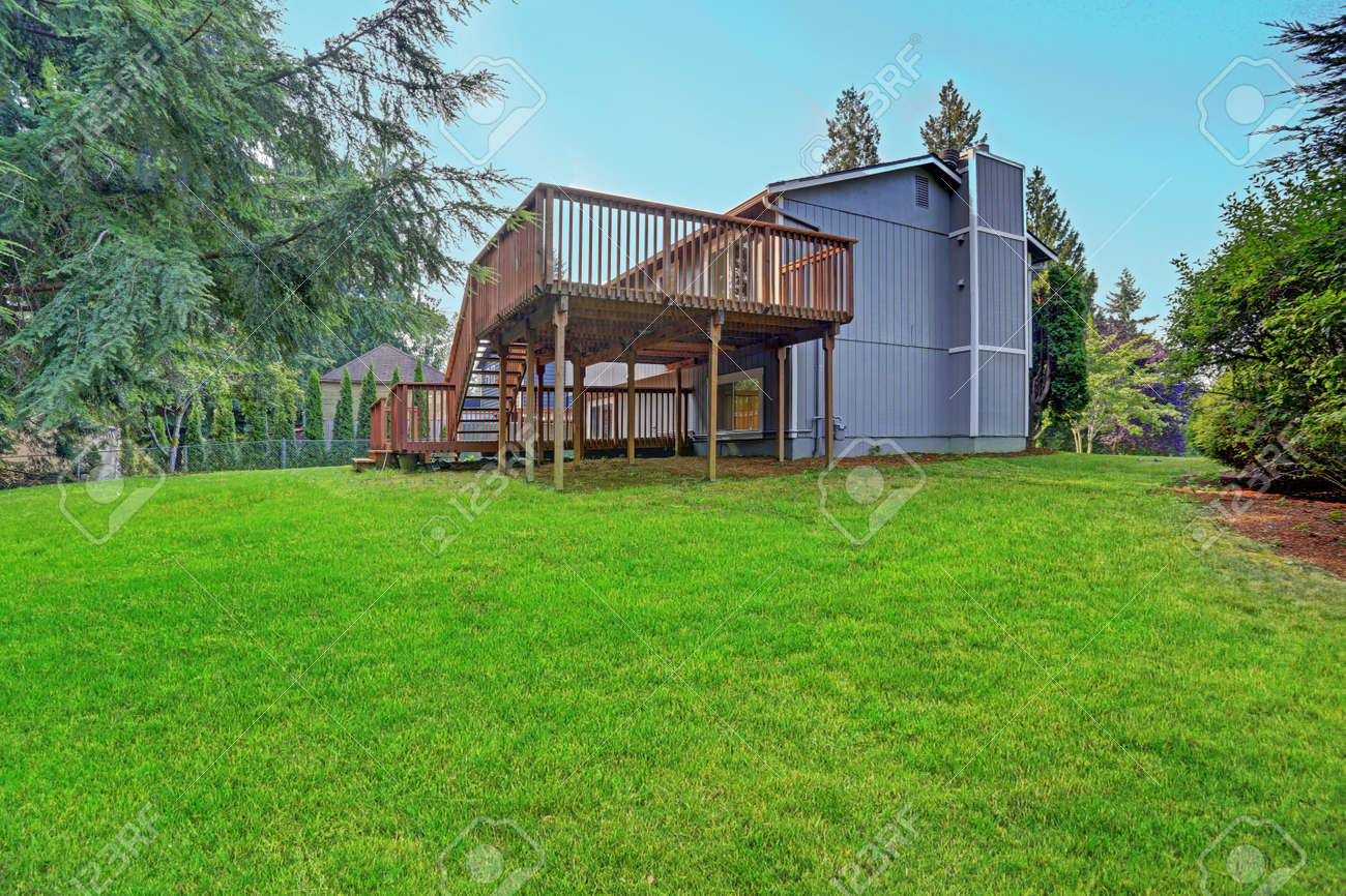 Backyard view of grey rambler house with upper and lower decks and green lawn. Kirkland, WA, USA. - 144812921