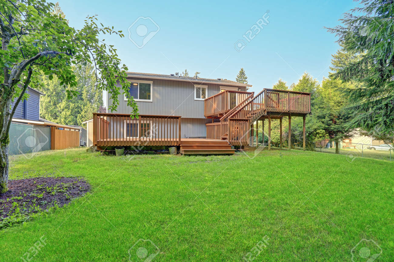 Backyard view of grey rambler house with upper and lower decks and green lawn. Kirkland, WA, USA. - 144812920