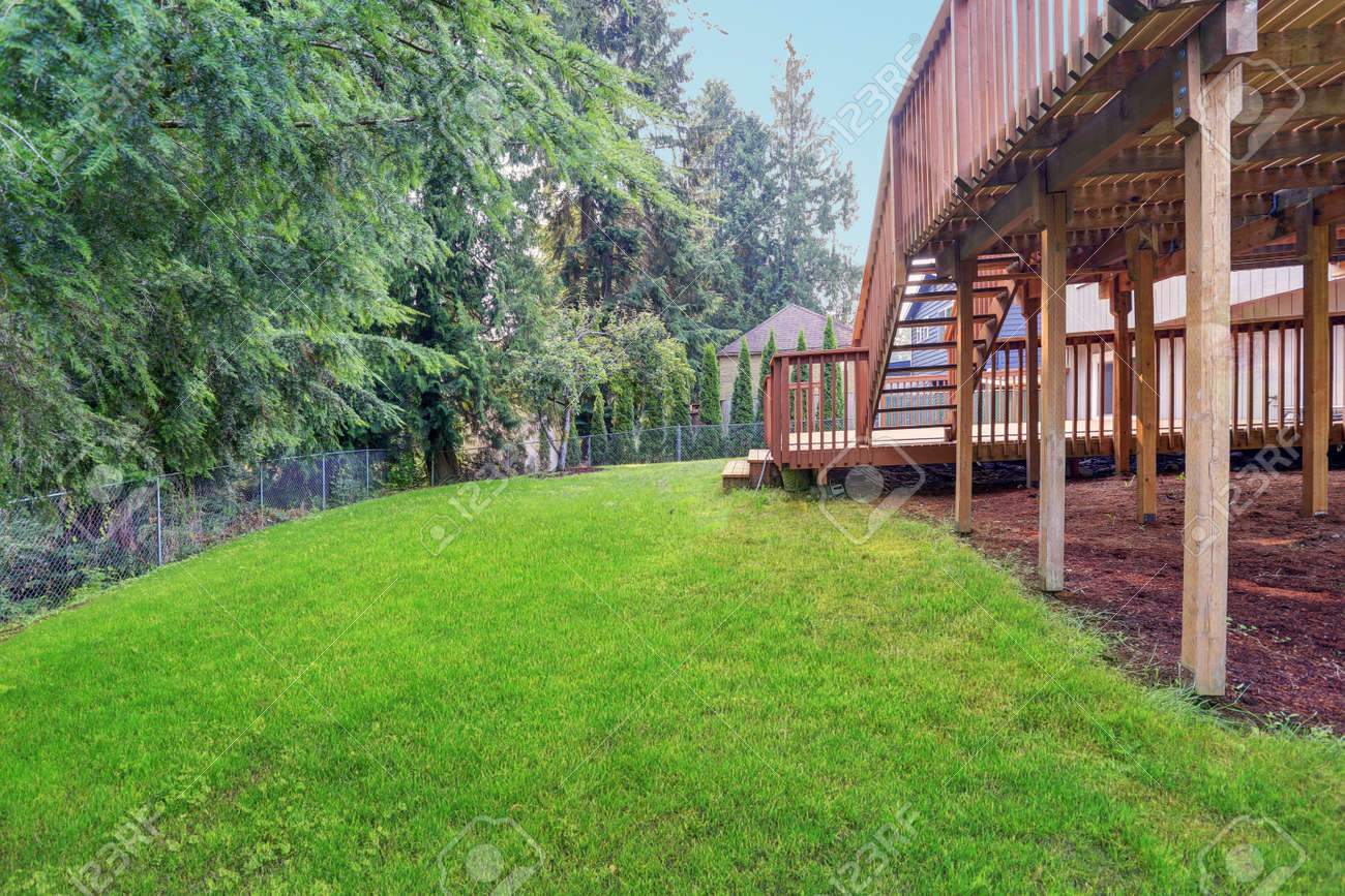 Backyard view of grey rambler house with upper and lower decks and green lawn. Kirkland, WA, USA. - 144812923